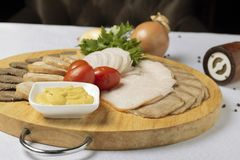 Assorted meat, cheese sauce and cherry tomatoes with onion rings stock photo
