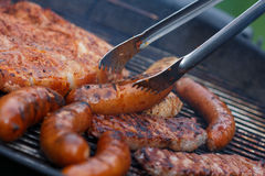 Assorted meat from chicken and pork and sausages on barbecue grill Royalty Free Stock Photography