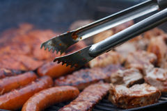 Assorted meat from chicken and pork and sausages on barbecue grill Royalty Free Stock Photo
