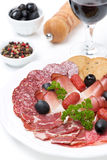 Assorted meat delicacies on a plate and a glass of wine Stock Photos