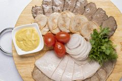 Cold cuts with parsley, cheese sauce and cherry tomatoes with onion rings stock photo