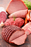 Assorted meat products including ham and sausages Stock Photos
