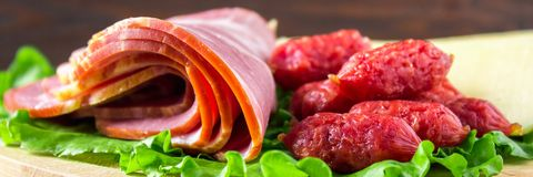 Assorted meat products including ham and sausages. cheese banner. Assorted meat products including ham and sausages. cheese stock photography