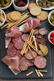 Assorted meat snacks and pickles on a blackboard, top view Royalty Free Stock Image
