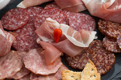 Assorted meat snacks, sausages on a blackboard, top view Royalty Free Stock Photo