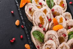 Assorted meat, stuffed chicken roll, meat roll with pomegranate, greens on black shale background. Meat appetizer, food concept. Top view royalty free stock images