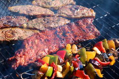 Assorted meat and vegetables on the grill. Lamb steaks, pork ribs, paprika and aubergine roasted on barbecue grid being cooked for summer family dinner Royalty Free Stock Images