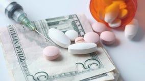 Assorted medical drugs , cash and syringe on color background.