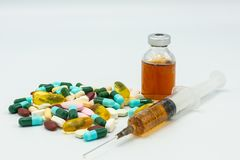 Assorted medicine with a syringe and glass vial filled yellow red solution stock photos