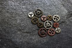 Metal gears concept. Assorted metal gears on a dark textured background, with copy space Stock Image