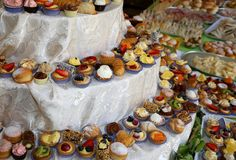 Assorted mignon pastries with creams and fruit on a buffet table. To celebrate a wedding royalty free stock photo