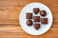 Assorted milk chocolate candy on a white plate on a wood background. For Valentine's Day royalty free stock images