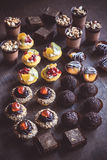 Assorted mini cakes on wooden background Royalty Free Stock Photos