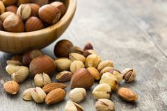 Assorted mixed nuts in bowl on wooden table Royalty Free Stock Images