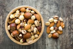 Assorted mixed nuts in bowl on wooden table Stock Photos