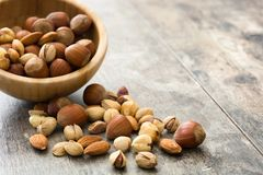 Assorted mixed nuts in bowl on wooden table Stock Photography