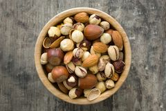 Assorted mixed nuts in bowl on wooden table Stock Image