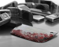 Assorted mobile phones with bloody knife weapon Royalty Free Stock Images
