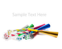 Assorted noise makers on white with copy space. Assorted noise makers including red, silver, yellow, green, blue on a white background with copy space royalty free stock images