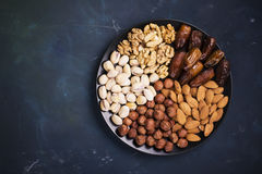 Assorted nuts, almonds, pistachios, walnuts, hazelnuts and figs on a black ceramic plate   dark background. Top view Royalty Free Stock Photos