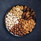 Assorted nuts, almonds, pistachios, walnuts, hazelnuts and figs on a black ceramic plate   dark background. Top view Stock Photography