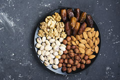 Assorted nuts, almonds, pistachios, walnuts, hazelnuts and figs on a black ceramic plate   dark background. Top view Stock Photos