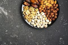 Assorted nuts, almonds, pistachios, walnuts, hazelnuts and figs on a black ceramic plate   dark background. Top view Stock Photo