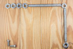 Assorted nuts and bolts square frame on wood texture background stock photography