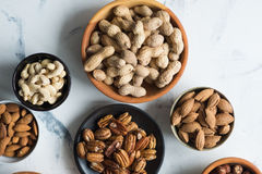 Mixed nuts in bowls. Assorted nuts in bowls on marble table, view from above stock images