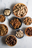 Mixed nuts  in bowls on marble table. Assorted nuts in bowls on marble table, view from above Royalty Free Stock Image