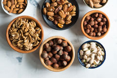 Mixed nuts  in bowls on marble table. Assorted nuts in bowls on marble table, view from above Stock Images