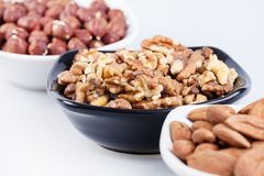 Assorted nuts in ceramic bowls Stock Photography