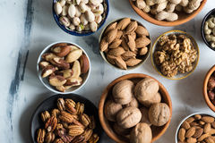 Mixed nuts  in bowls on marble table. Assorted nuts in different bowls on marble table, view from above Stock Photography