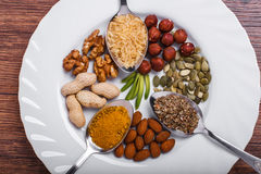 Assorted nuts in white bowl, plate on wooden surface. Top view with copy space Royalty Free Stock Photos