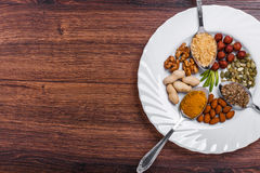Assorted nuts in white bowl, plate on wooden surface. Top view with copy space Royalty Free Stock Images