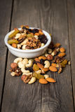 Assorted nuts in white bowl on wooden background. Stock Image