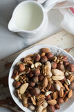 Mixed nuts in ceramic bowl. Assorted nuts in white ceramic bowl on wooden surface Stock Photos