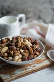 Mixed nuts in white bowl. Assorted nuts in white ceramic bowl on wooden surface Royalty Free Stock Photography