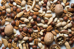 Mixed nuts closeup. Assorted nuts on white surface royalty free stock images