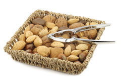 Assorted nuts in a wicker basket with a nutcracker stock photo