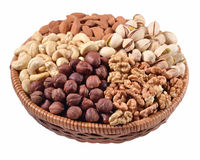 Assorted nuts in a wicker bowl on a white background Royalty Free Stock Photos