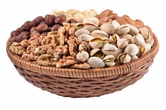 Assorted nuts in a wicker bowl on a white background Royalty Free Stock Image