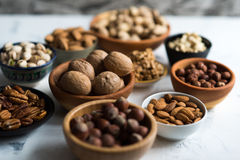 Mixed nuts  in bowls on marble table. Assorted nuts in wooden bowls on white surface Stock Photography