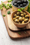 Assorted olives with oregano on the kitchen board  on the white wooden table Stock Photos
