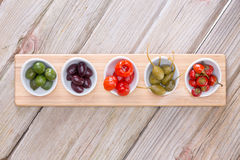 Assorted olives and peppers on taster plates. View from above of a line of assorted cured savory olives and peppers in individual taster plates on a wooden board Stock Photos