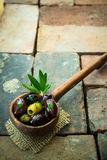 Assorted olives in a wooden ladle Stock Images