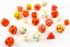 Assorted Orange Yellow And White Dice. An assortment of orange yellow and white dice in a variety of shapes and sizes photographed on a white background Royalty Free Stock Photography