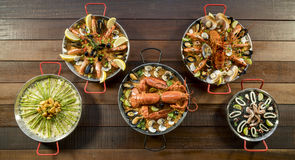 Assorted paella on wooden table, above view Royalty Free Stock Photo