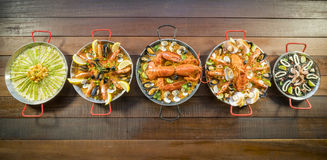 Assorted paella on wooden table, above view Royalty Free Stock Photography