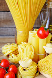 Assorted pasta and red tomatoes Stock Images